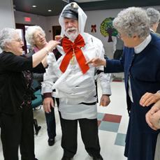 Photo d'une équipe en train de déguiser un participant en bonhomme de neige lors d'une fête de Noël